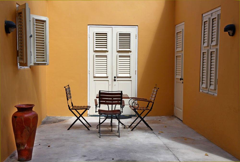 Patio con paredes amarillas y una mesa con sillas - Sillas de patio ...